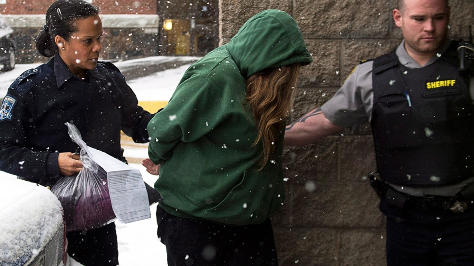 Melissa Merritt is escorted at provincial court in Halifax on Wednesday, Jan. 29, 2014. (Andrew Vaughan / THE CANADIAN PRESS)