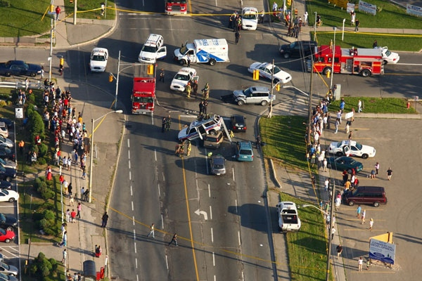 A crowd gathered after a spectacular collision involving a police vehicle on Victoria Park Ave. in Toronto, Tuesday, July 15, 2008. (Tom Podolec for CTV.ca)
