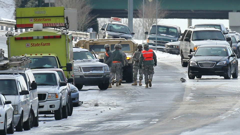 Georgia National Guard troops in humvees and a HERO unit check on a stranded motorists and search abandoned vehicles to give aid to those still stuck on the highway at Roswell Road and I-285 on Wednesday afternoon, Jan. 29, 2014. (/Atlanta Journal-Constitution, Curtis Compton)