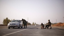 A rebel fighter, left, checks a car at a checkpoint between Tarhouna and Bani Walid, Libya, Monday, Sept. 5, 2011. (AP / Alexandre Meneghini)
