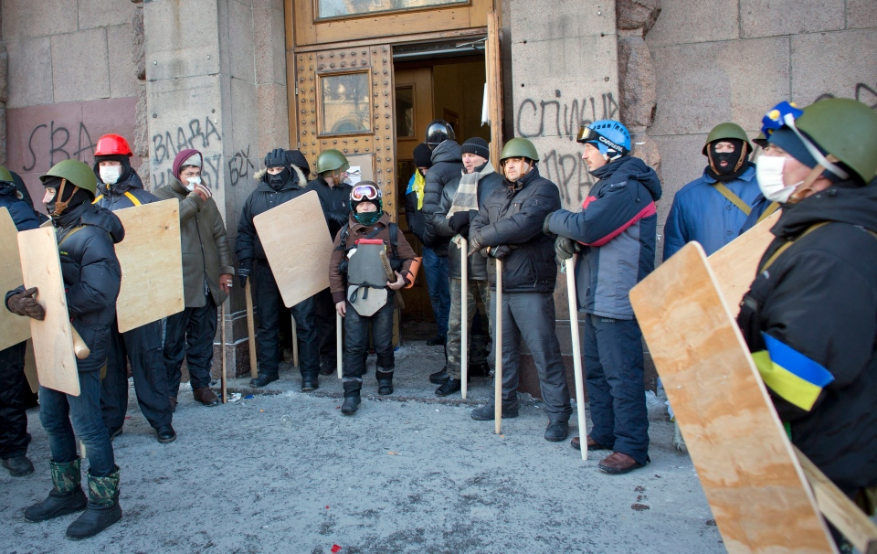 Protesters armed with wooden sticks and shields stand outside a building in central Kyiv, Wednesday, Jan. 29, 2014. (AP / Darko Bandic)