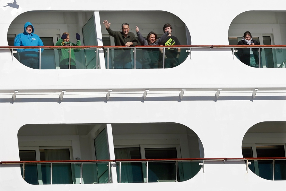 Passengers wave from the Explorer of the Seas cruise ship as it docks at a berth in Bayonne, N.J., Wednesday, Jan. 29, 2014. (AP / Mel Evans)