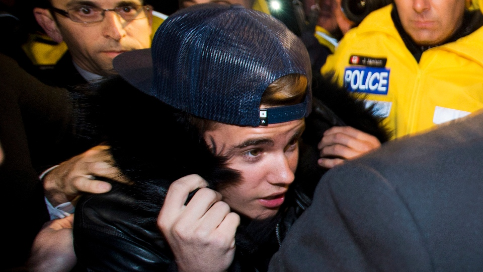 Canadian musician Justin Bieber is swarmed by media and police officers as he turns himself into city police in Toronto on Wednesday, January 29, 2014. (THE CANADIAN PRESS / Nathan Denette)
