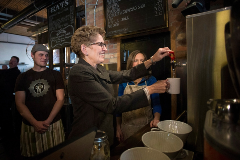 Ontario Premier Kathleen Wynne makes herself a cup of tea at a Toronto coffee shop, before making an announcement regarding the minimum wage in the province, Thursday, Jan. 30 , 2014. (Chris Young / THE CANADIAN PRESS)