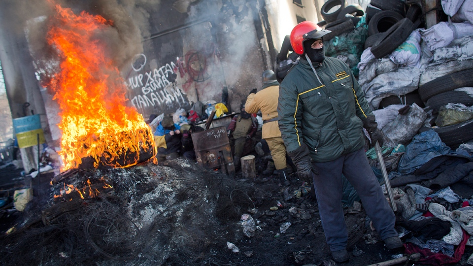 A protester armed with a metal stick stands next to a burning tire on a barricade in central Kyiv, Ukraine, Thursday, Jan. 30, 2014. (AP / Darko Bandic)