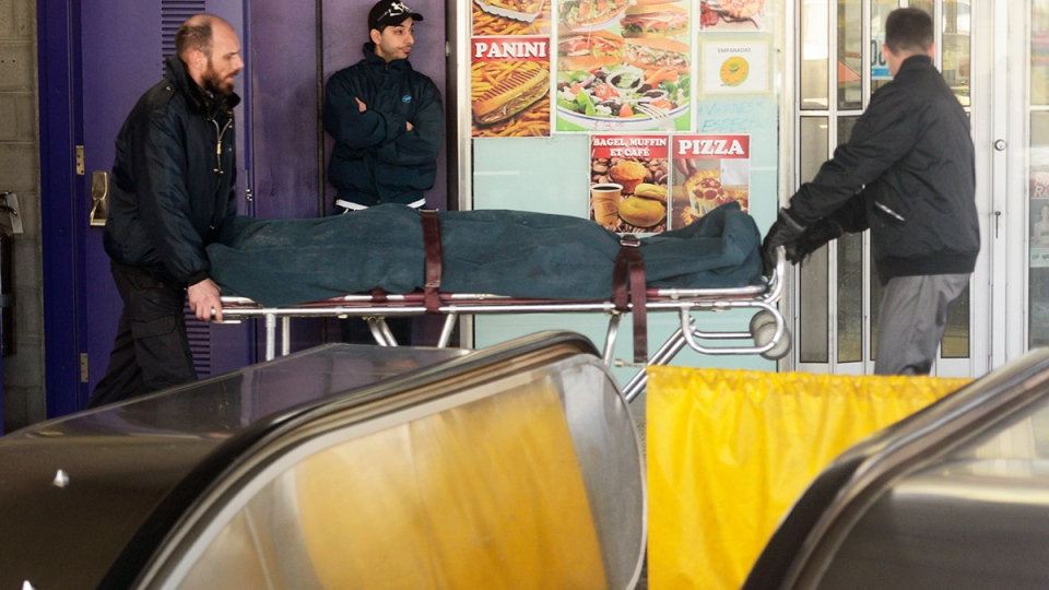 Workers remove the body of a woman after an escalator accident in Montreal on Thursday, Jan 30, 2014. (Ryan Remiorz / THE CANADIAN PRESS)