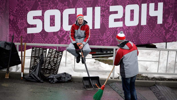 Two workers take a break at the Sanki Sliding Center, a venue for bobsleigh, skeleton and luge at the 2014 Winter Olympics in Krasnaya Polyana, Russia, Friday, Jan. 31, 2014. (AP / Jae C. Hong)
