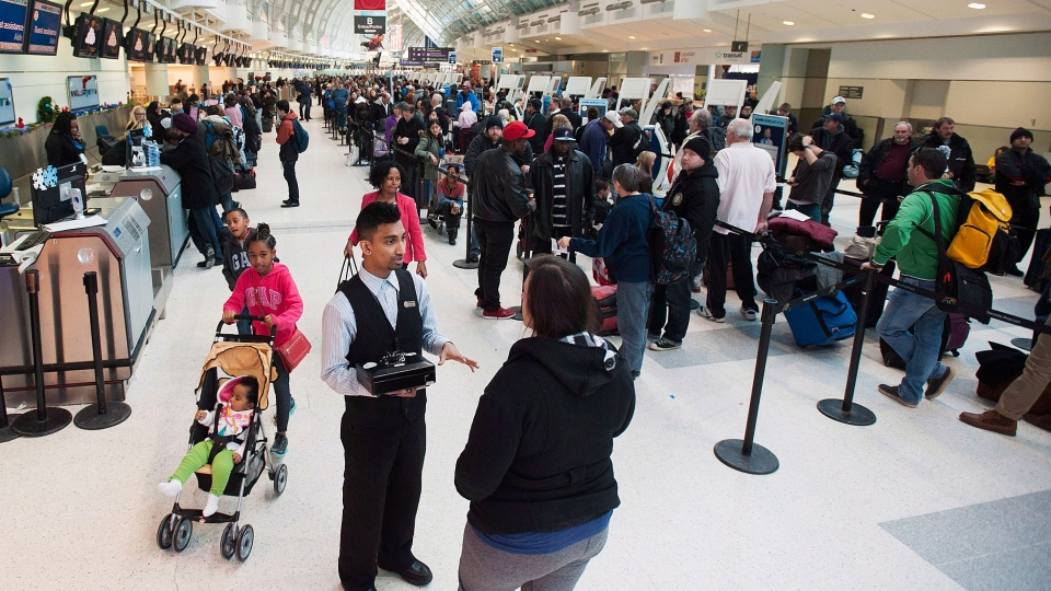 Passengers line-up at Toronto Pearson's Terminal 3. Canada's electronic spy agency is defending itself against accusations it tracked the wireless devices at Canada's airports. (Aaron Vincent Elkaim / THE CANADIAN PRESS)