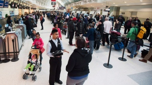 Passengers line-up at Toronto Pearson's Terminal 3. (Aaron Vincent Elkaim / THE CANADIAN PRESS)
