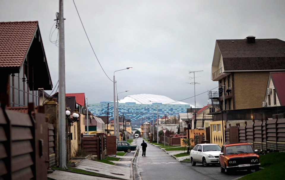 A man walks down the street as the roof of the Fisht Olympic Stadium is seen in the background, Friday, Jan. 31, 2014, in Sochi, Russia. (AP / David Goldman)