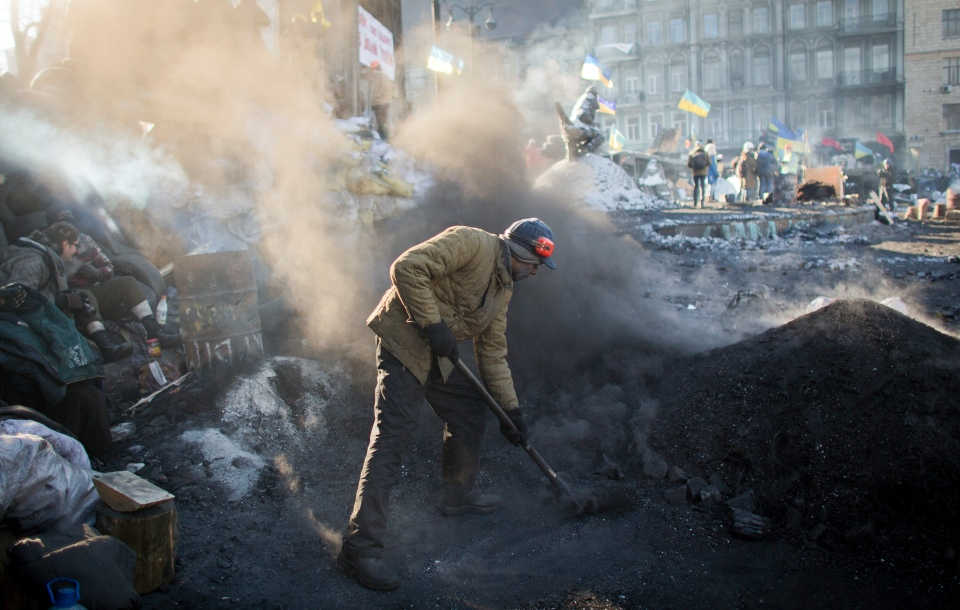 An anti-government activist collects ashes from burnt tyres at a barricade in central Kyiv, Ukraine, Friday, Jan. 31, 2014. (AP / Darko Bandic)