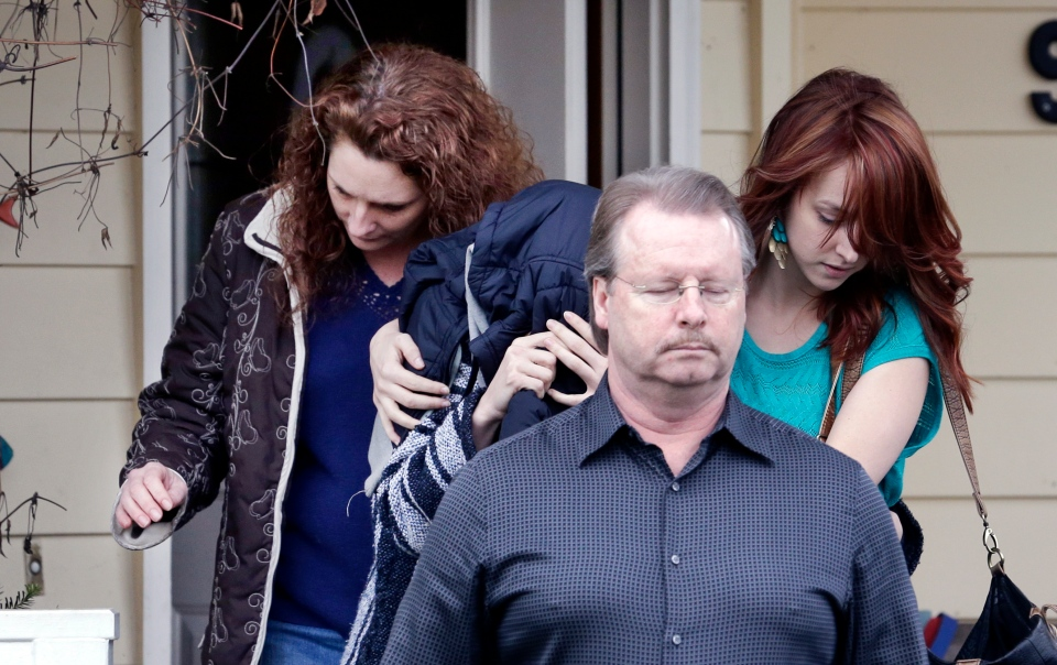 A woman believed to be Amanda Knox, centre left, is hidden under a jacket while being escorted from Knox's mother's home to a car by family members in Seattle, Thursday, Jan. 30, 2014. (AP)