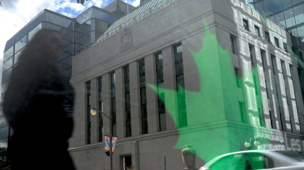 The Bank of Canada is reflected in signage on a bus stop in Ottawa on Tuesday, Sept. 6, 2011. (Sean Kilpatrick / THE CANADIAN PRESS)