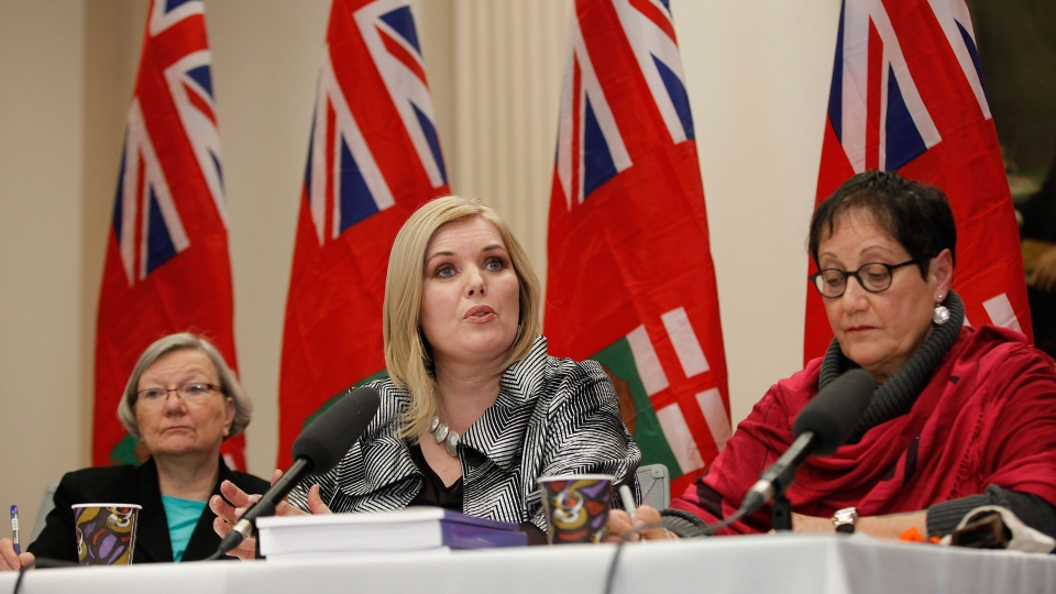 Family Services Minister Kerri Irvin-Ross (centre) speaks to media regarding the release of the Phoenix Sinclair Inquiry Report as Carolyn Loeppky (left), assistant deputy minister in the department of Family Services, and Barbara Bruce, leader of the implementation team, listen in at the Manitoba Legislature in Winnipeg, Friday, January 31, 2014. (John Woods / THE CANADIAN PRESS)