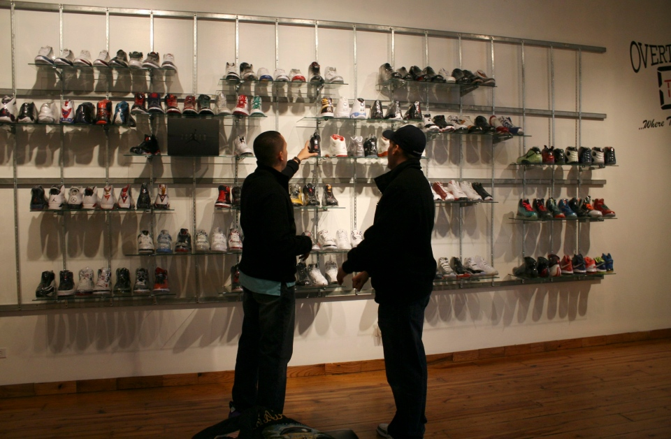 "In this photo taken Feb. 28, 2012, Jesus ""Jstar"" Estrella, left, a blogger who follows the ""sneakerhead"" scene, checks out shoes with his cousin at a Chicago consignment store called Overtime.  (AP Photo/Martha Irvine)"