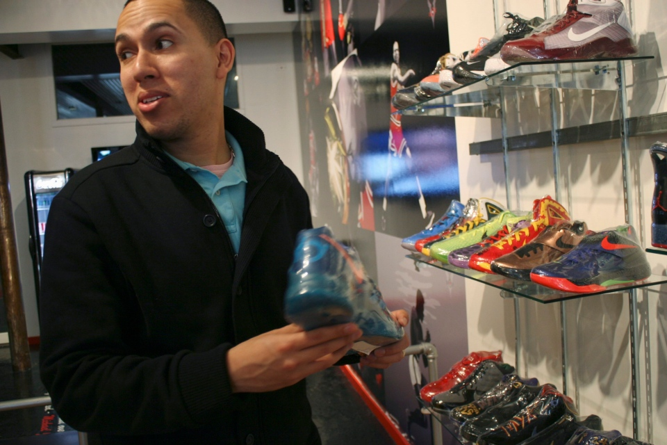 "In this photo taken Feb. 28, 2012, Jesus ""Jstar"" Estrella, a blogger who follows the ""sneakerhead"" scene, checks out shoes with his cousin at a Chicago consignment store called Overtime. (AP Photo/Martha Irvine)"