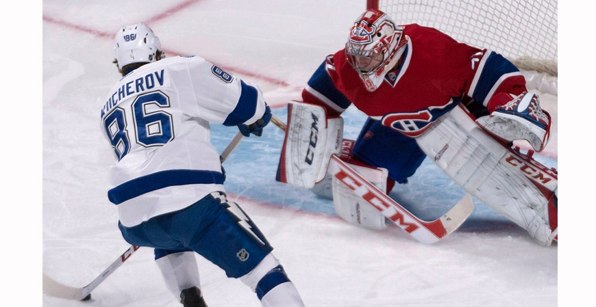Montreal Canadiens goalie Carey Price eyes the puck as Tampa Bay Lightning Nikita Kucherov, of Moscow, tries to score during a penalty shot in first period NHL action in Mntreal Saturday, February 1, 2014. THE CANADIAN PRESS/Peter McCabe