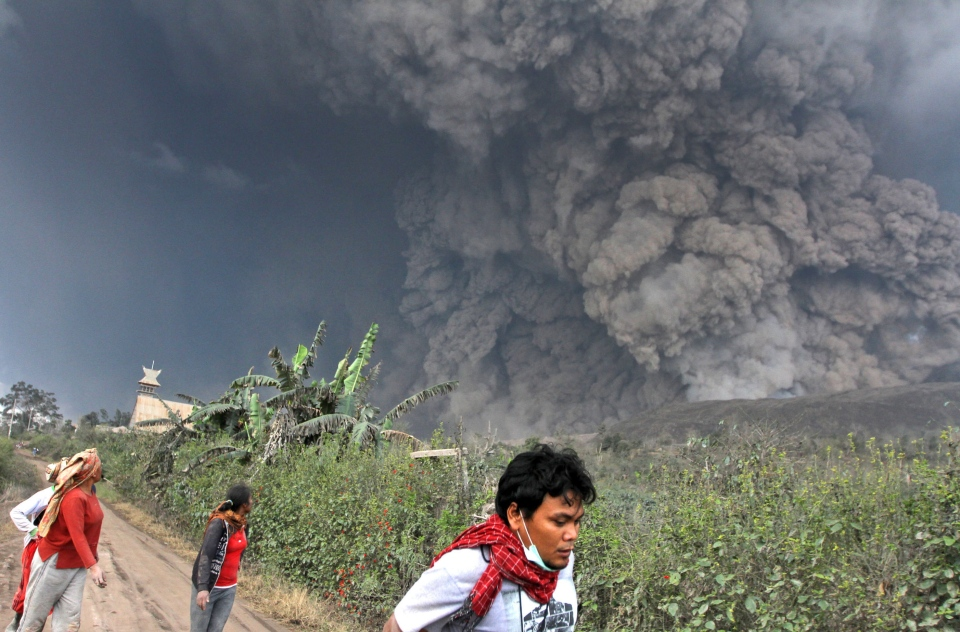 Villagers and a journalist prepare to flee as Mount Sinabung releases pyroclastic flows during an eruption in Namantaran, North Sumatra, Indonesia on Feb. 1, 2014. (AP)