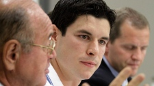 Pittsburgh Penguins' Sidney Crosby, center, and Dr. Michael Collins, right, listen as Dr. Ted Carrick, left, describes Crosby's progress in his recovery from a concussion he suffered in January 2011 during an NHL hockey news conference in Pittsburgh on Wednesday, Sept. 7, 2011. (AP / Gene J. Puskar)