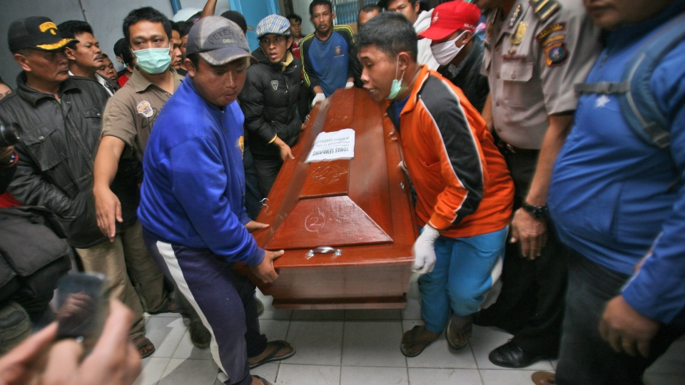 Relatives carry a coffin containing the body a victim of the eruption of Mount Sinabung, at a hospital in Kabanjahe, North Sumatra, Indonesia, Saturday, Feb. 1, 2014. (AP / Binsar Bakkara)