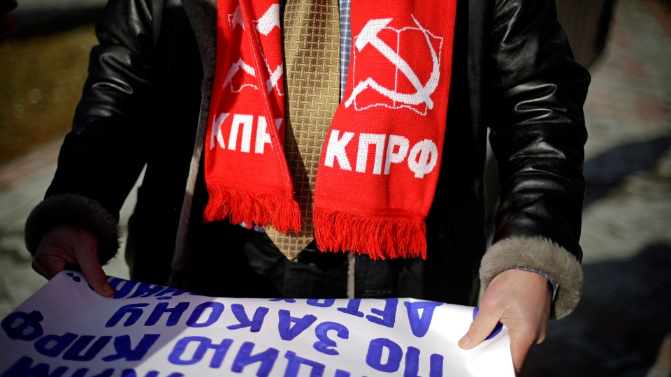 Igor Vasiliyev, head of the local branch of the Communist Party, wears a scarf decorated with a hammer and sickle, a symbol of the communist movement, as he leads a protest in the 50 Years of Victory in the Great Patriotic War Park to hold the first official demonstration in the designated Olympic protest area for the 2014 Winter Olympics, in Sochi, Russia, Saturday, Feb. 1, 2014. (AP / David Goldman)