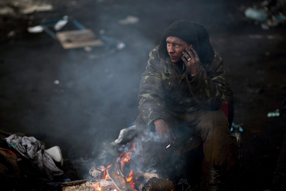 An opposition supporter uses his cellphone as he guards a barricade outside Kiev's Independence Square, the epicenter of the country's current unrest, Ukraine, Sunday, Feb. 2, 2014. (AP / Emilio Morenatti)
