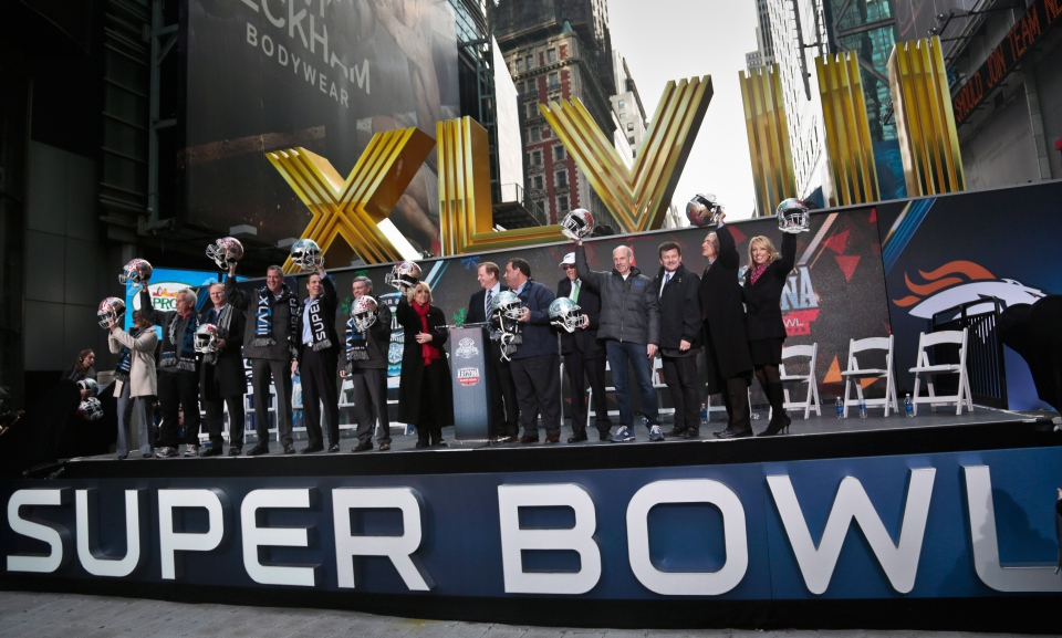 Officials from New York, New Jersey, and Arizona raise souvenir football helmets during a ceremony to pass official hosting duties of next year's Super Bowl to representatives from Arizona on New York's Super Bowl Boulevard, Saturday Feb. 1, 2014. (AP / Bebeto Matthews)