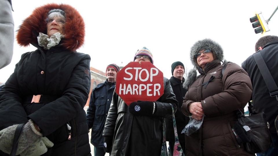 Mary Hutchings holds a 'Stop Harper' placard while gathering with veterans and supporters outside the Veterans Affairs Office in Brandon, Manitoba, on Friday, Jan. 31, 2014. (Tim Smith / THE CANADIAN PRESS)