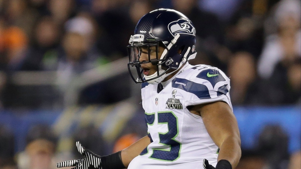 Seattle Seahawks' Malcolm Smith (53) puts the ball under his jersey after recovering a fumble during the second half of the NFL Super Bowl XLVIII football game against the Denver Broncos in East Rutherford, N.J., Sunday, Feb. 2, 2014. (AP / Jeff Roberson)