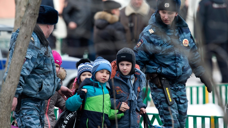 Police officers evacuate children from a Moscow school on Monday, Feb. 3, 2014. (AP Photo/Alexander Zemlianichenko)