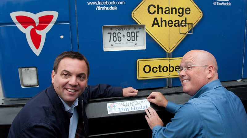 Ontario Progressive Conservative Leader Tim Hudak and Leeds-Grenville MPP Steve Clark put a bumper sticker on Hudak's campaign bus in Brockville, Ont., on Sept. 7, 2011. (Lars Hagberg / THE CANADIAN PRESS)