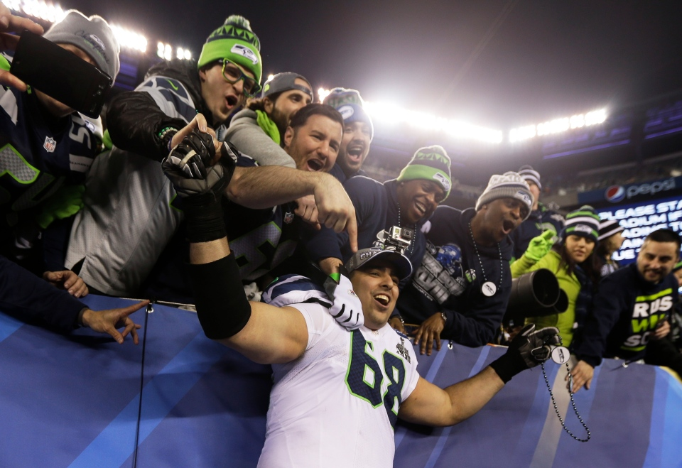 Seattle Seahawks' Breno Giacomini celebrates with fans after the NFL Super Bowl XLVIII football game against the Denver Broncos in East Rutherford, N.J., Sunday, Feb. 2, 2014. (AP / Jeff Roberson)