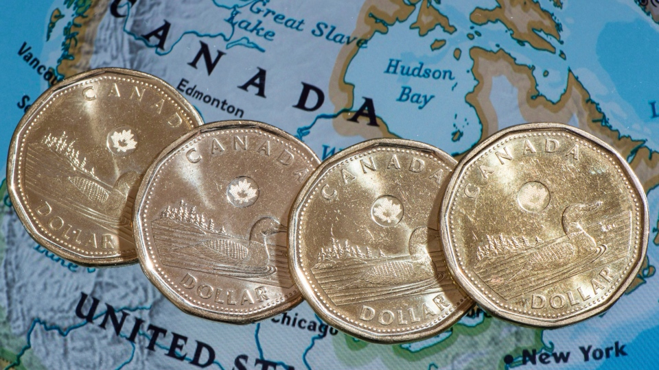 Loonies are displayed on a map of North America in this file photo from Thursday, Jan. 9, 2014. (Paul Chiasson / THE CANADIAN PRESS)