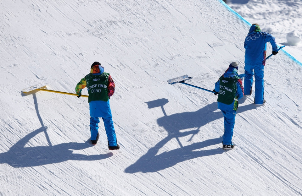 Course workers groom a jump during a ski slopestyle training session at the Rosa Khutor Extreme Park, prior to the 2014 Winter Olympics, Tuesday, Feb. 4, 2014, in Krasnaya Polyana, Russia. (AP / Sergei Grits)