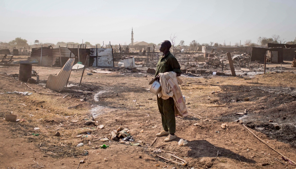 A man carrying his belongings stands amongst the remains of buildings destroyed by the recent fighting, after government forces on Friday retook from rebel forces the provincial capital of Bentiu, in Unity State, South Sudan on Sunday, Jan 12, 2014. (AP / Mackenzie Knowles-Coursin)