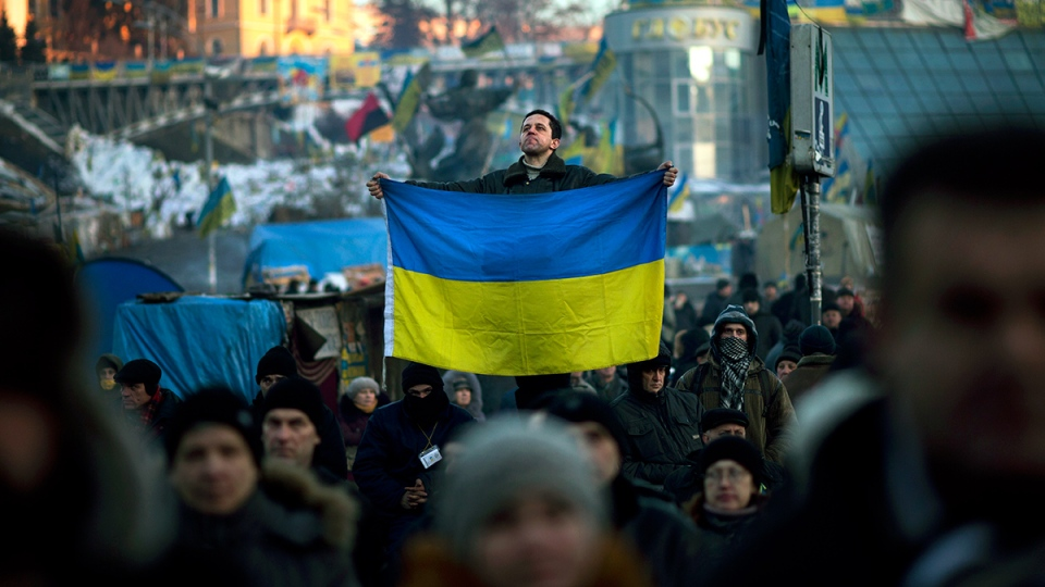 A man holds an Ukrainian flag in the centre of Independence Square, the epicenter of the country's current unrest, in Kyiv, Ukraine, Tuesday, Feb. 4, 2014. (AP / Emilio Morenatti)