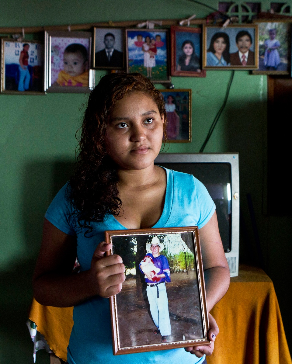 Fatima Alvarenga, the daughter of Jose Salvador Alvarenga, poses for a portrait holding a photograph of herself held by her father when she was a baby, at her family's home in the village of Garita Palmera, El Salvador, Tuesday, Feb. 4, 2014. (AP / Esteban Felix)