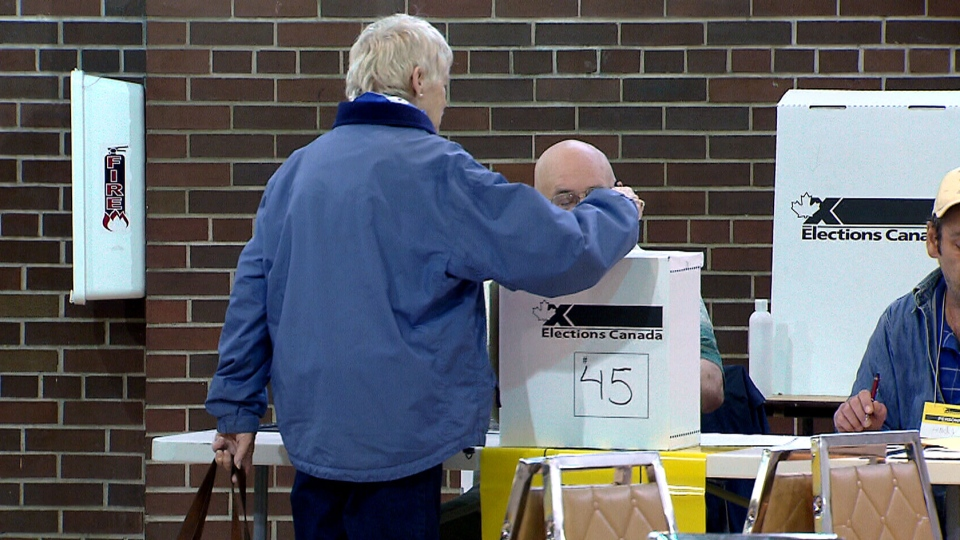 A woman places her vote at an election in Canada.