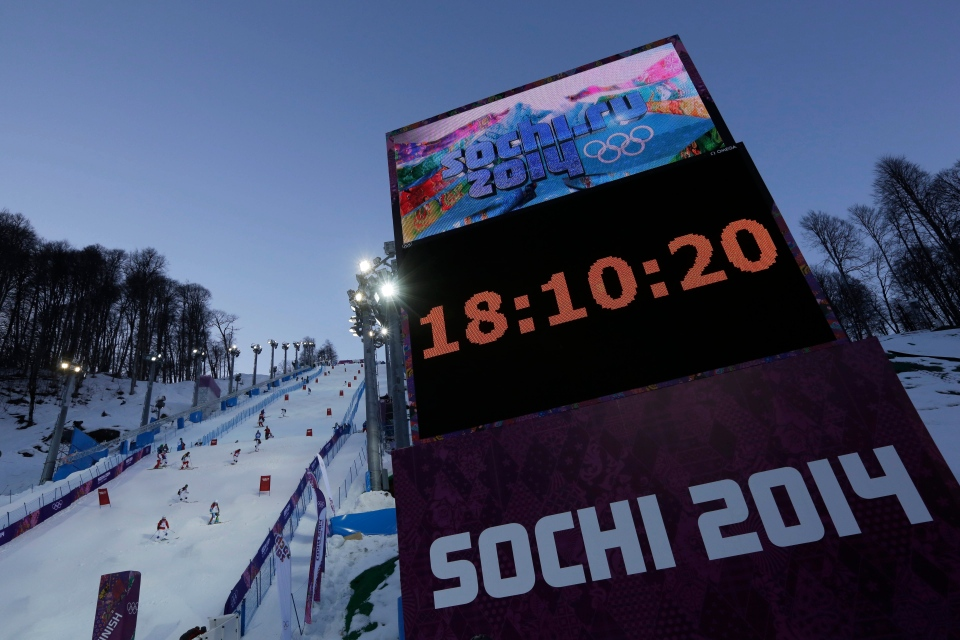 Competitors check the course near a display board before a moguls training session at the Rosa Khutor Extreme Park, prior to the 2014 Winter Olympics, Tuesday, Feb. 4, 2014, in Krasnaya Polyana, Russia. (AP/Andy Wong)