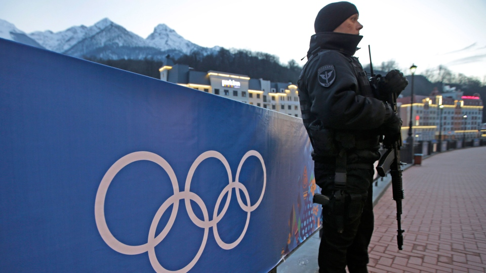 An armed Russian security guard stands at the ski resort Rosa Khutor, where the snow and sliding sports venues for the 2014 Winter Olympics are located, Tuesday, Feb. 4, 2014, in Krasnaya Polyana, Russia. (AP / Dita Alangkara)