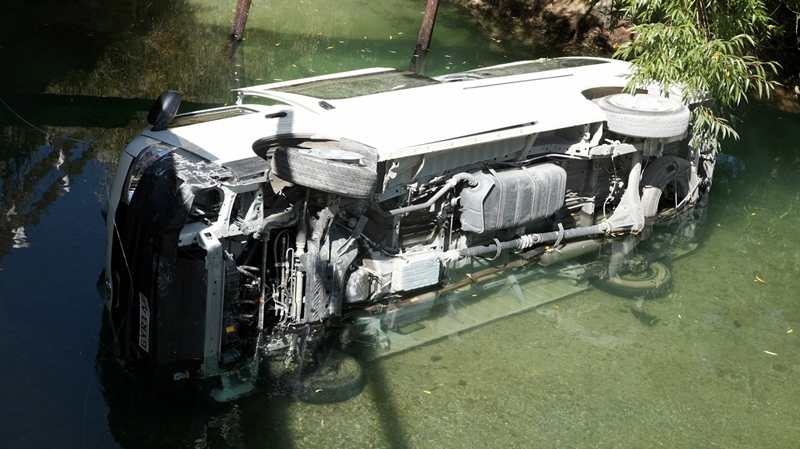 In this photo provided by New Zealand Police, a minivan lies on its side in the Mataura River, 110 kilometres north of Invercargill on the South Island of New Zealand Wednesday, Feb. 5, 2014. (AP Photo/New Zealand Police)