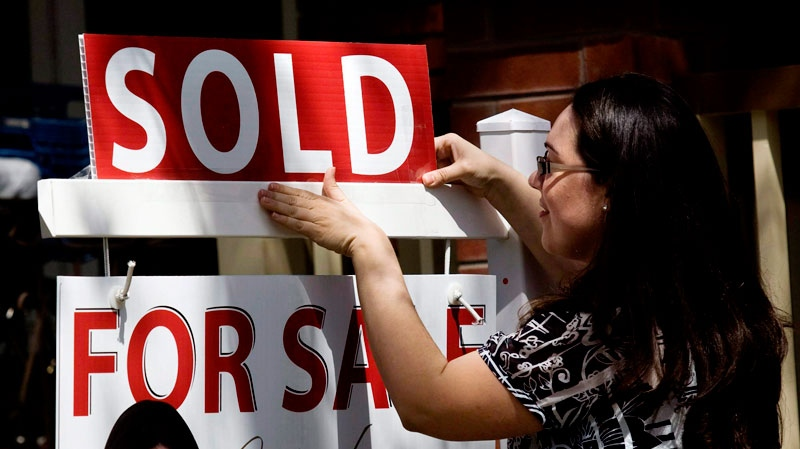 A real estate agent puts up a 'sold' sign in front of a house in Toronto on April 20, 2010. (Darren Calabrese / THE CANADIAN PRESS)