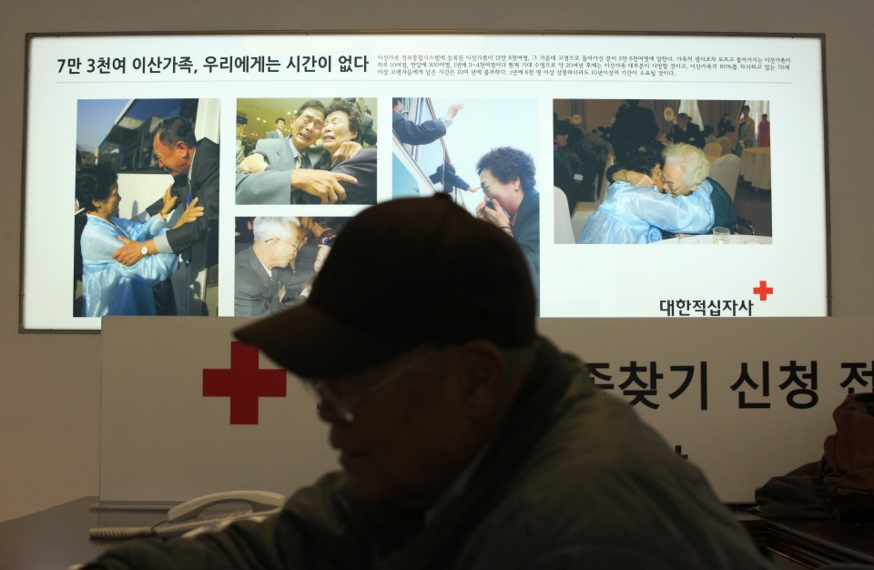 South Korean Kim Kwang-il, 86, fills out application forms to reunite with their family members who live in North Korea, in front of the pictures showing the reunion of family members from North and South Korea, at the headquarters of the Korea Red Cross in Seoul, South Korea, Wednesday, Feb. 5, 2014. (AP / Ahn Young-joon)