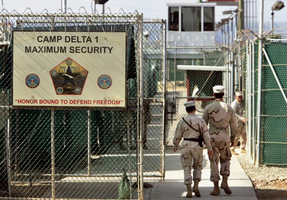 In this June 27, 2006 file photo, reviewed by a U.S. Department of Defense official, U.S. military guards walk within Camp Delta military-run prison, at the Guantanamo Bay U.S. Naval Base, Cuba. (AP / Brennan Linsley)