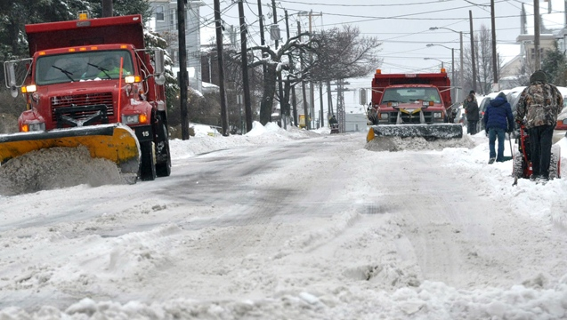 As residents dig out their cars, workers from the Department of City Works drive in tandem plowing the snow from West Diamond Avenue in Hazleton, Pa., on Wednesday, Feb. 5, 2014. (AP / Hazleton Standard-Speaker Ellen F. O'Connell)