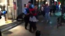 This blurry image from the video shows a police officer grabbing a woman just before she is pushed into a nearby bicycle post.