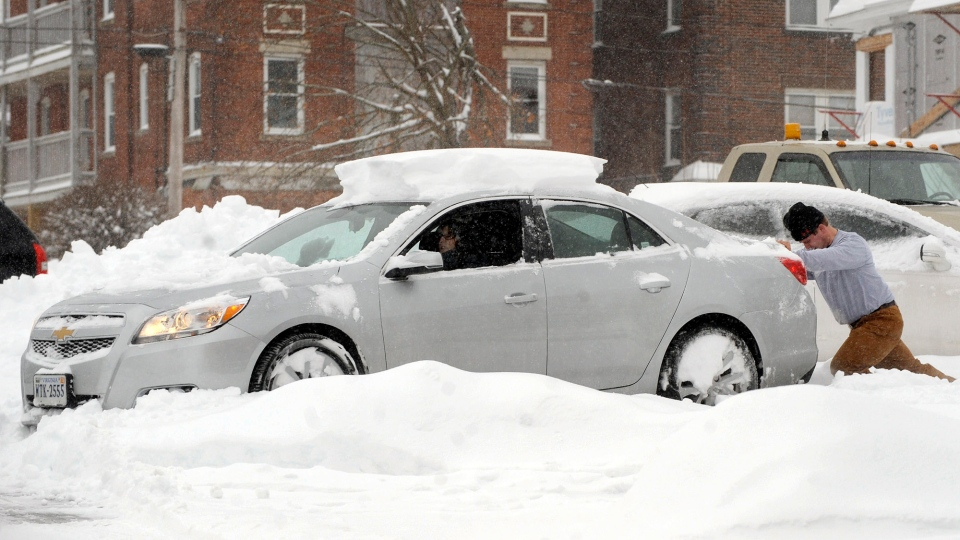 Good samaritan Eric Kobos, of Windsor Locks, Conn., comes to the aid of motorist Carol Derucki, of Enfield, Conn., after her car got stuck in the snow in the parking lot of her apartment building, Wednesday, Feb. 5, 2014, in Enfield, during the winter storm that left about 10 inches of snow in the area. (AP Photo/Journal Inquirer, Jim Michaud)