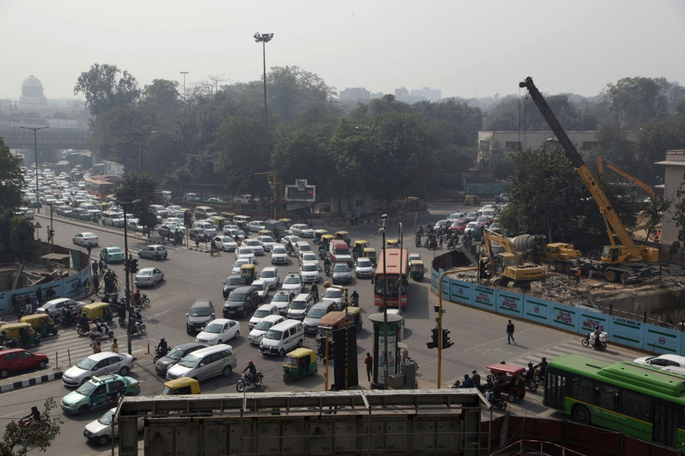 Vehicles move past a Delhi Metro construction site, right, in the morning in New Delhi, India, Wednesday, Feb. 5, 2014. On bad days in India's congested capital, the air is so murky it slows traffic to a crawl because visibility is so poor. (AP Photo/Tsering Topgyal)