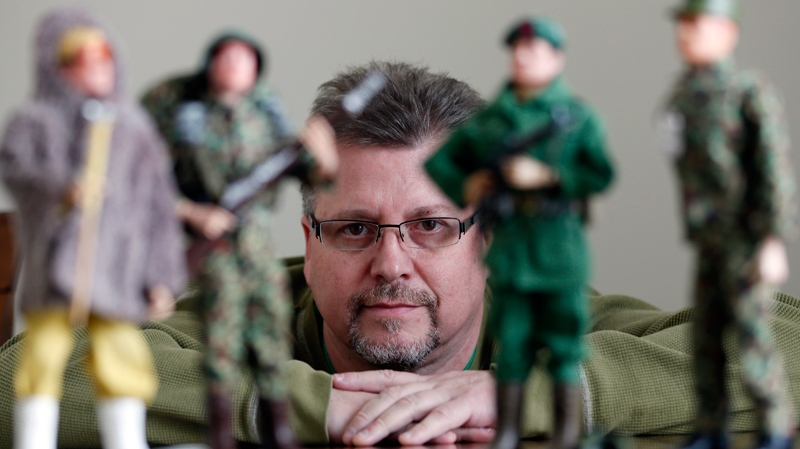 In this Jan. 31, 2014 photo Tearle Ashby poses with some of his G.I. Joe action figures in Niskayuna, N.Y.  (AP Photo/Mike Groll)