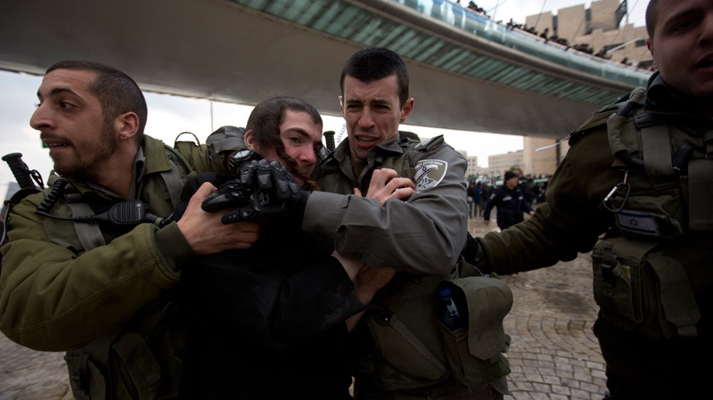 Israeli border police officers detain an ultra-Orthodox Jewish man during a demonstration in Jerusalem, Thursday, Feb. 6, 2014. (AP Photo/Sebastian Scheiner)